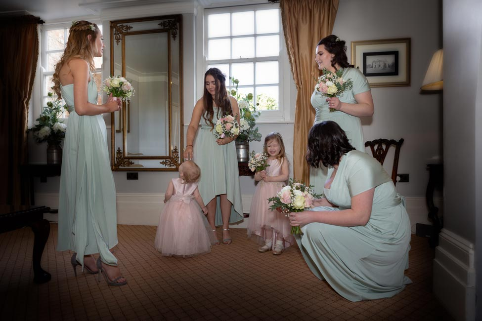 Bridesmaids doing last-minute preparations just before Sarah and Tom's Fennes wedding
