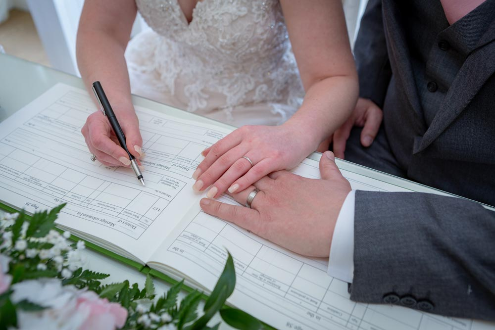 Bride and groom signing the register during a Fennes wedding