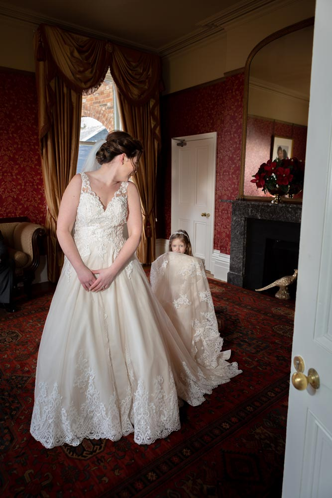 Flower girl helping to hold up the brides dress at the Fennes wedding venue