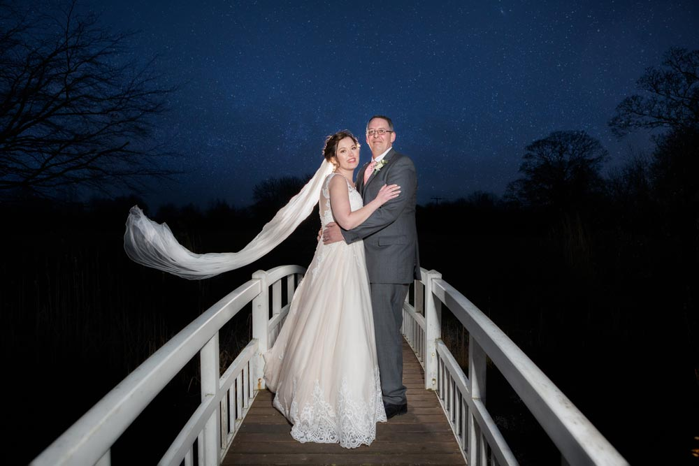 Bride and groom under the stars on the bridge at Essex wedding venue The Fennes