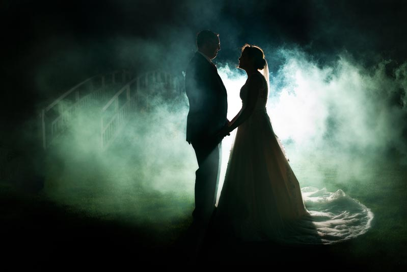 Bride and Groom silhouette image against a smoke-filled background