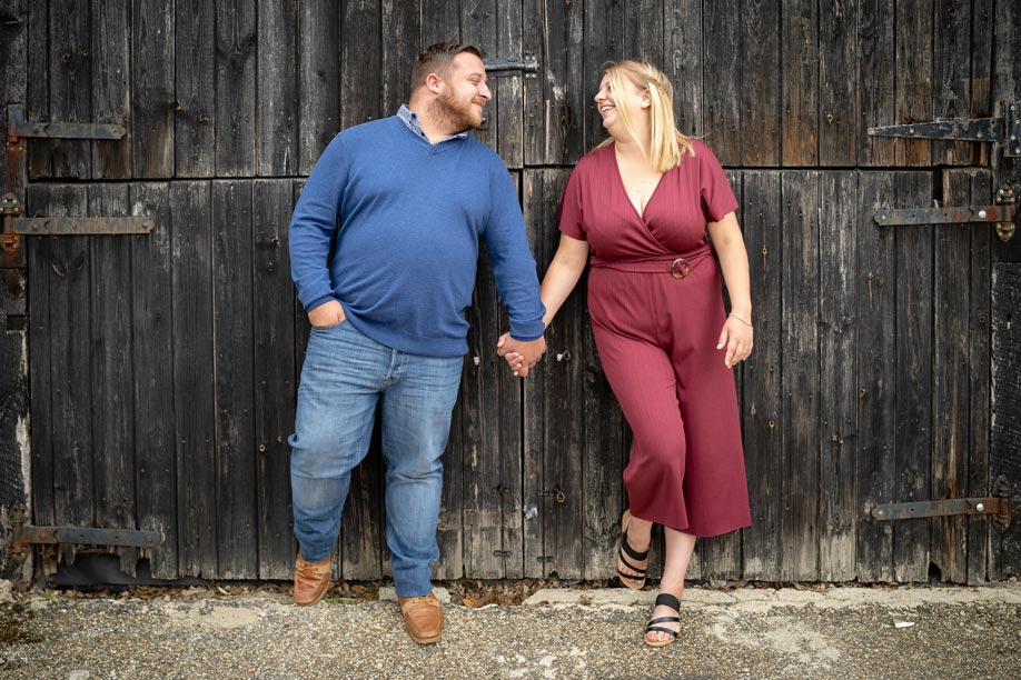 Engaged couple in front of the barn doors at All Manor of Events