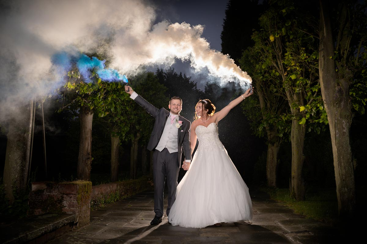 Bride and Groom letting off smoke grenades in the gardens at Quendon Hall