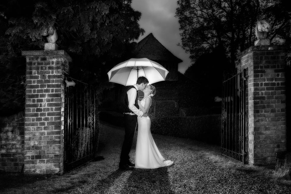 Bride and groom under an umbrella in front of the brick pillars at Colville Hall