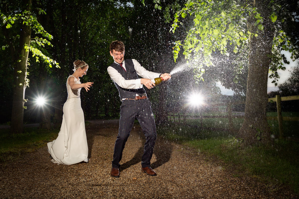 Bride and groom popping the cork on a bottle of bubbly