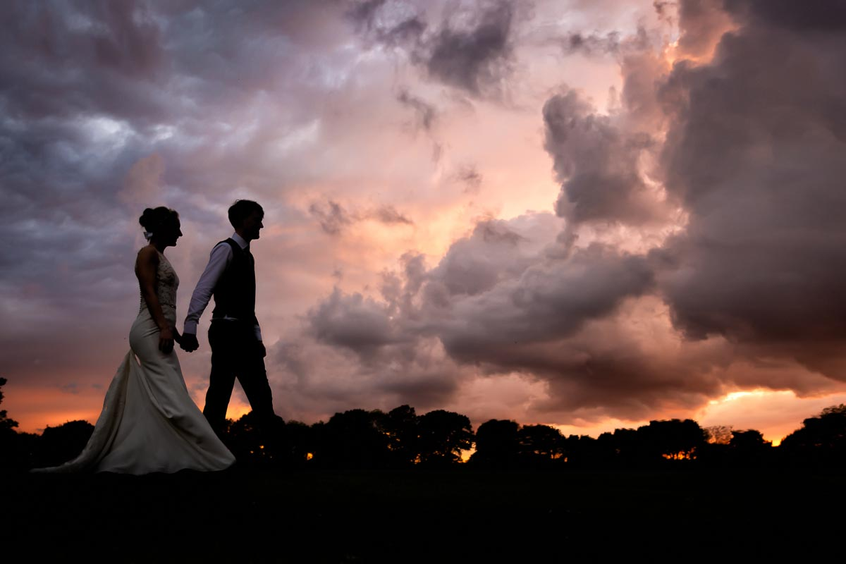 Bride and groom walking in silhouette with a beautiful sunset in the background at Colville Hall
