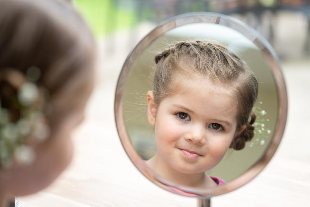 Flower girl looking in the mirror after having her hair done
