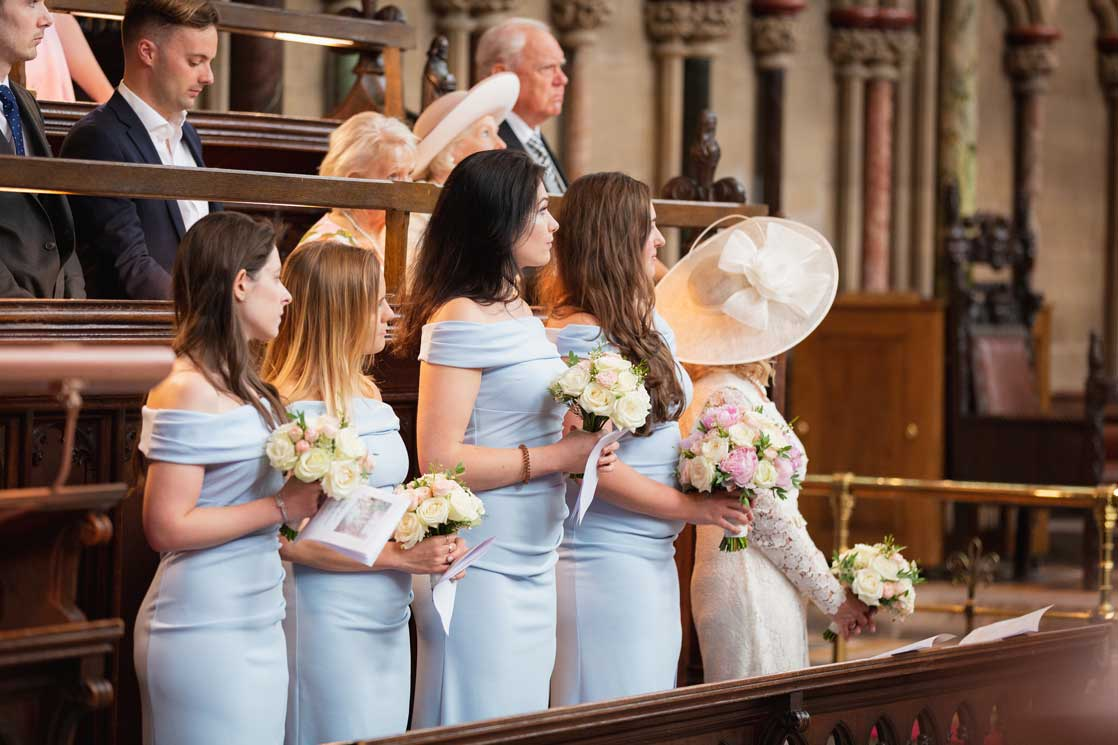 Bridesmaids in the pews at the St Johns College chapel, Cambridge