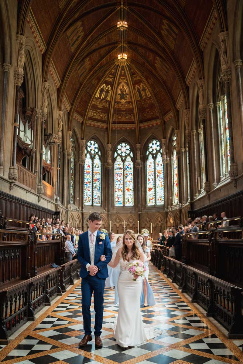 Bride and groom walking down the aisle at St Johns College Chapel in Cambridge