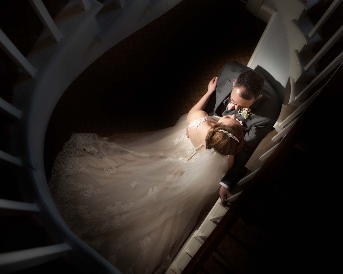 Bride and groom by the Fennes staircase
