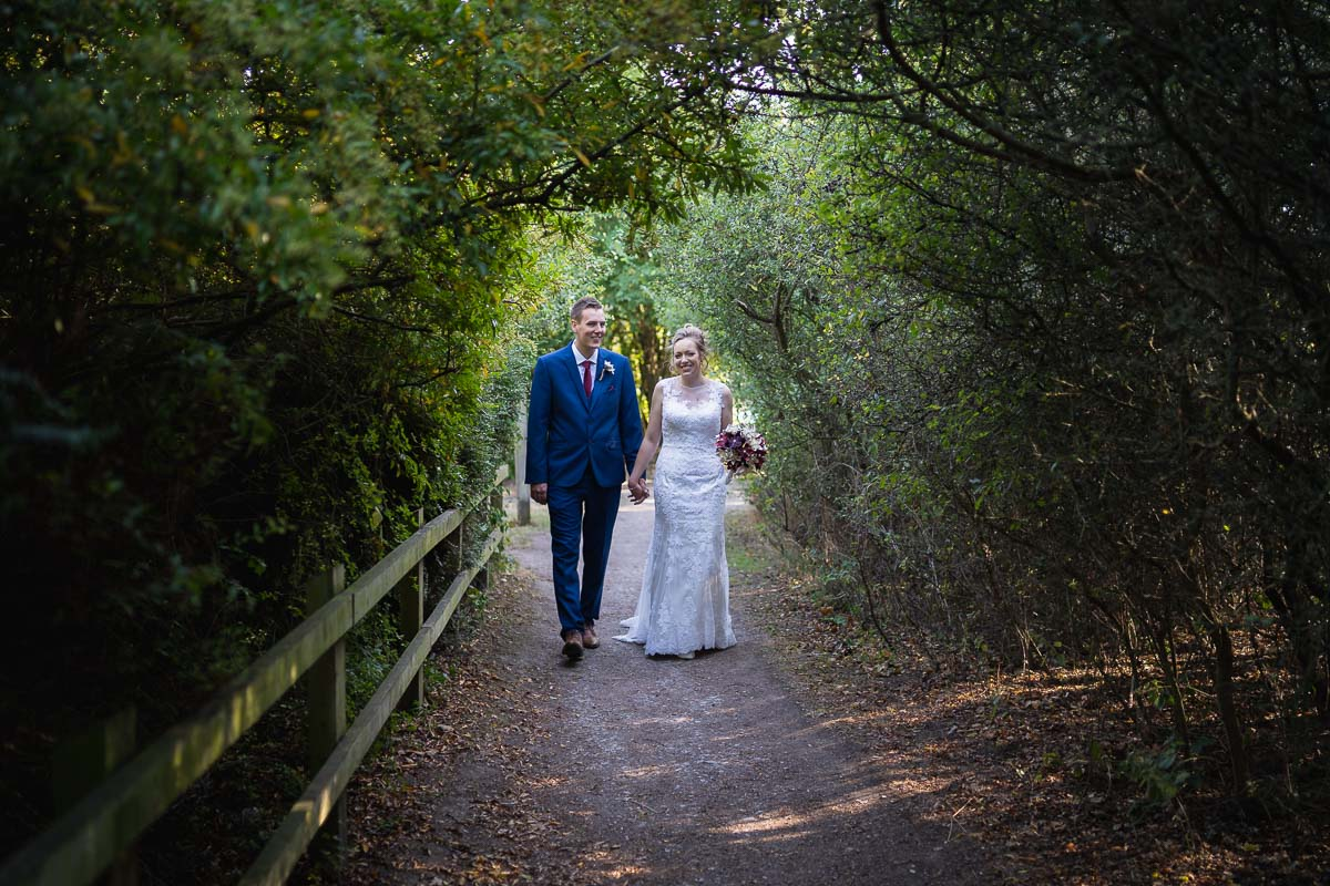 Bride and groom walking under the trees during their wedding at Wat Tyler Country Park