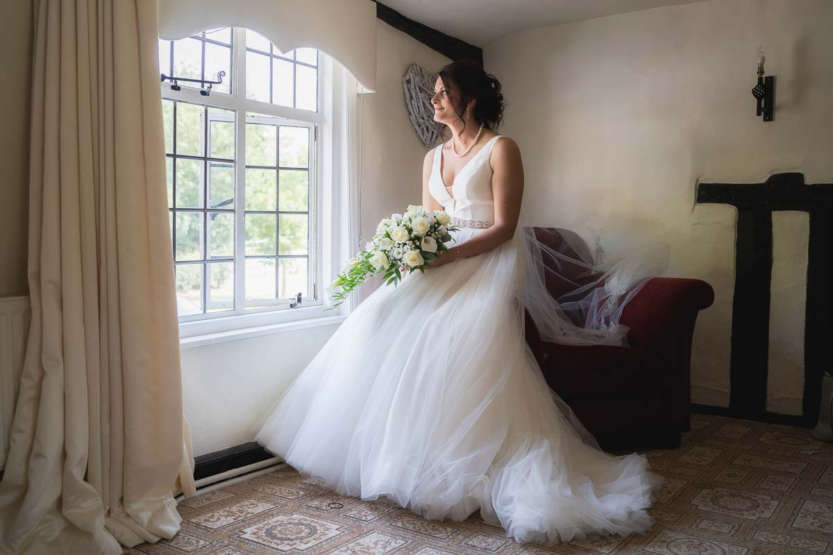 A bridal portrait of the bride looking out the window of the bridal suite at The White Hart at Great Yeldham