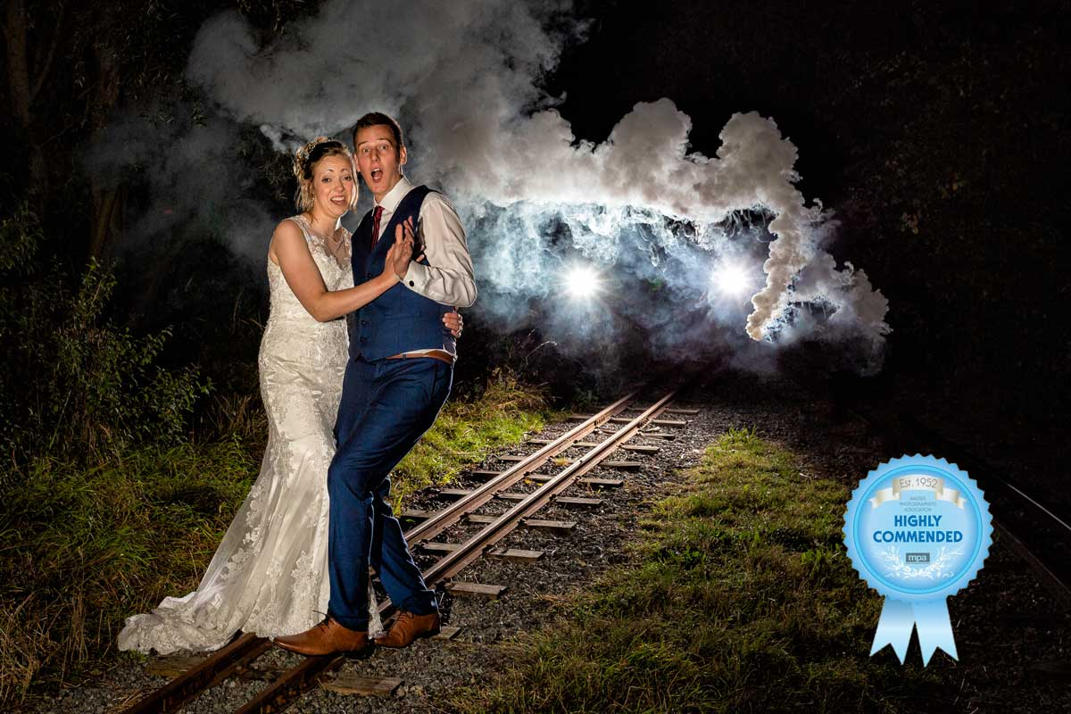 Bride and groom on the railway track looking scared as a train is coming during their wedding at Wat Tyler Country Park