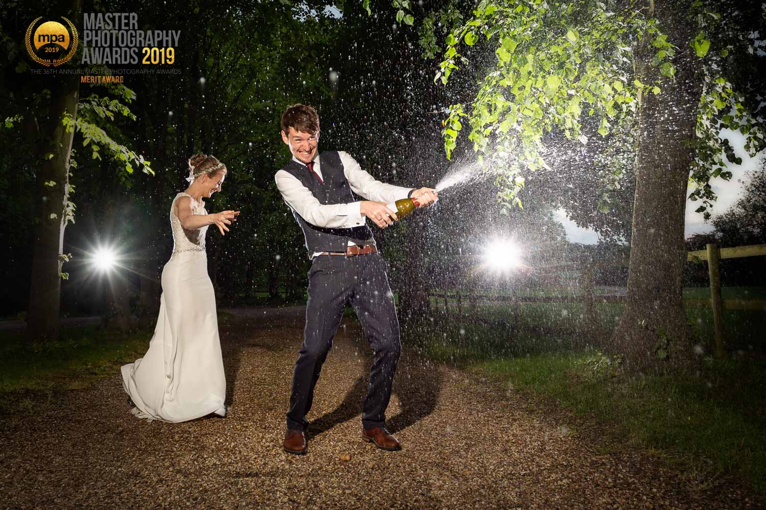 Newly married couple spraying champagne on their wedding day at Colville Hall in Essex