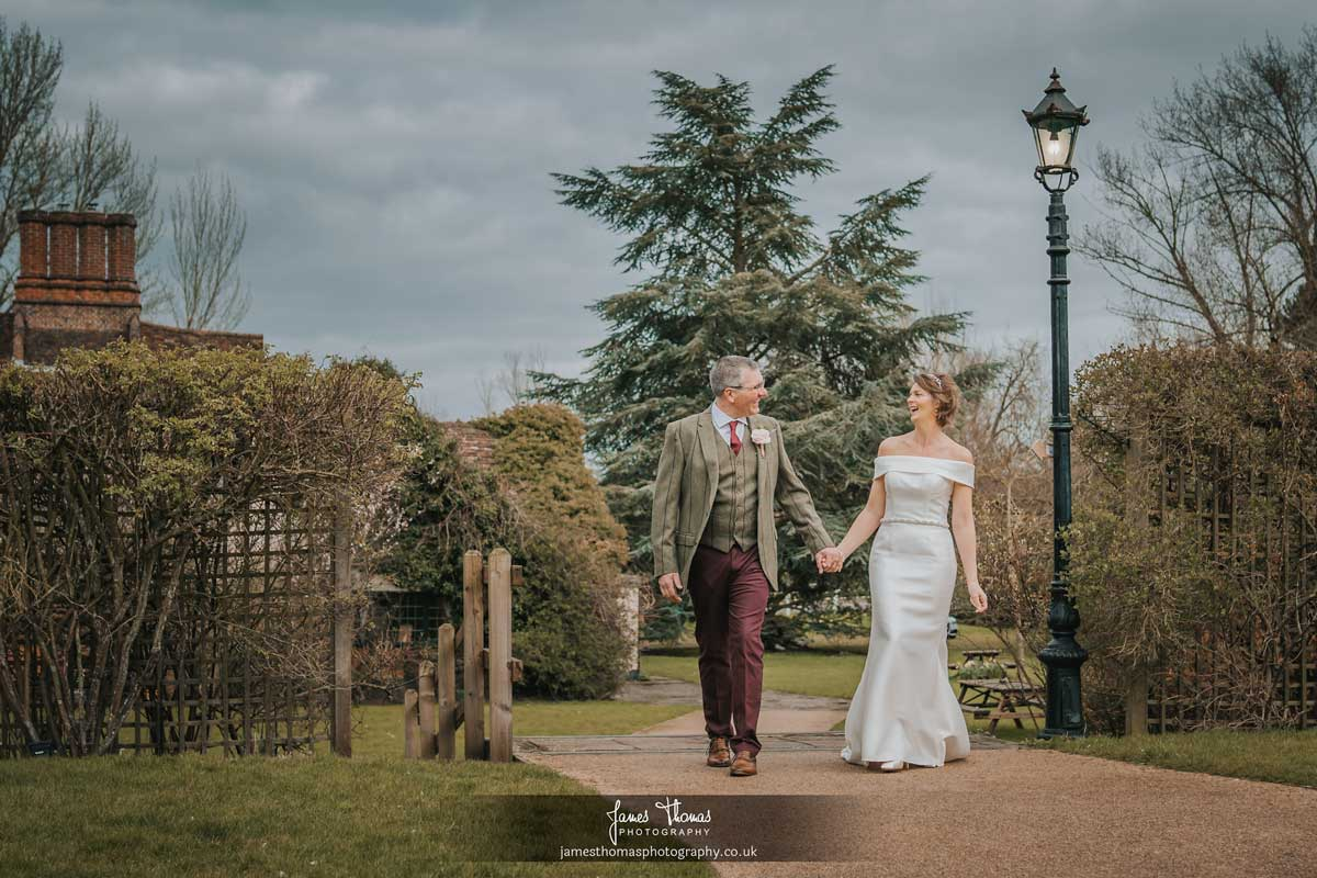 Bride and groom walking through the gardens at The White Hart in Great Yeldham