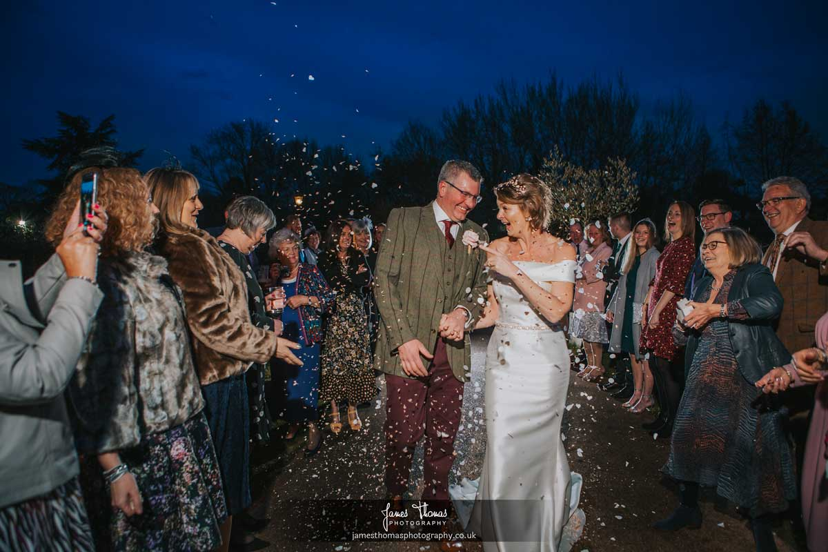 Bride and groom walking at night while guests throw confetti at The White Hart in Great Yeldham.