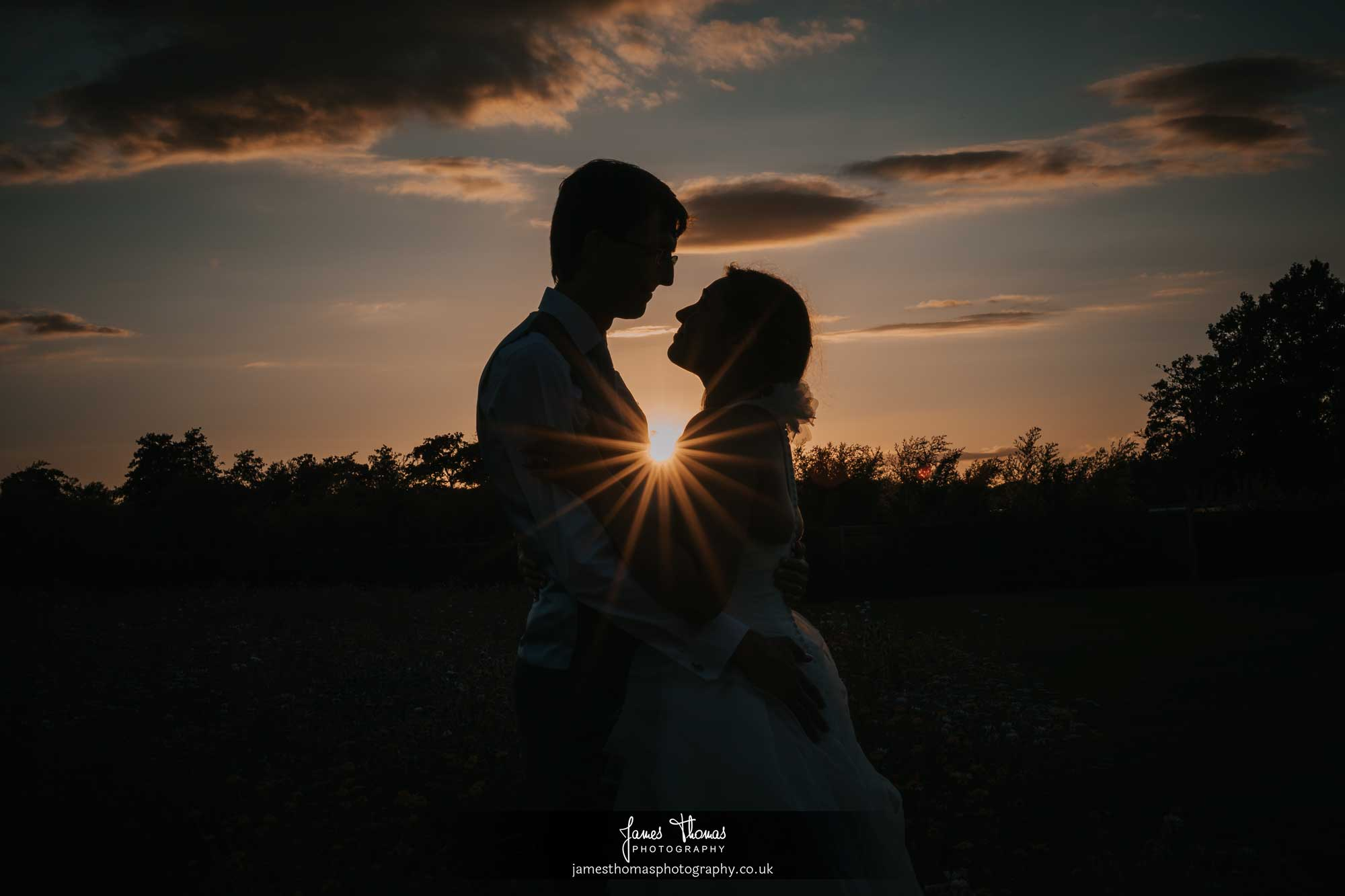 Silhouette of bride and groom with the sun star bursting between them